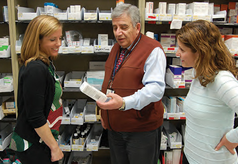 From left, Michelle Baytarian, Tony Hourgnieh, and Rayhme Collins in the pharmacy looking at some medications