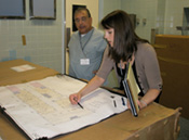 Two staff members reviewing a floor plan